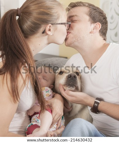 A young couple s kissing . A dog and the baby is between the two lovers. - stock photo