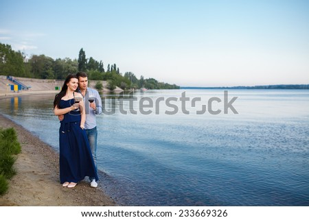 A young couple share a romantic dinner with candles and wine glasses on the sea sand beach - stock photo