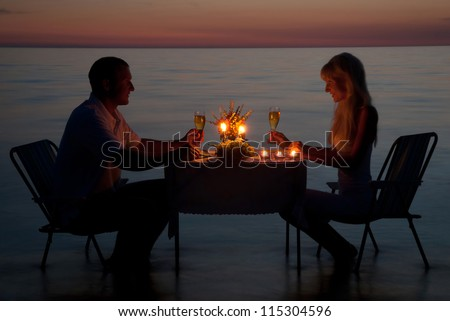 A young couple share a romantic dinner with candles on the sea sand beach - stock photo