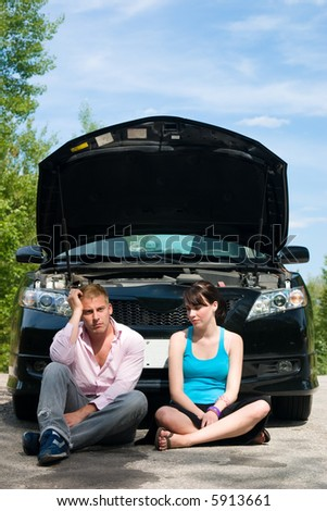 A young couple sits dejectedly as their car breaks down - stock photo