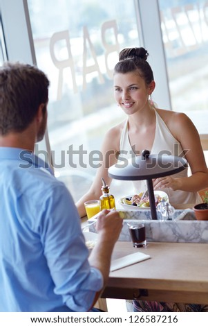 A young couple sitting at a table and have lunch at an outdoor restaurant - stock photo