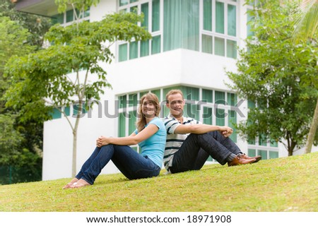 A young couple sitting in garden of their house