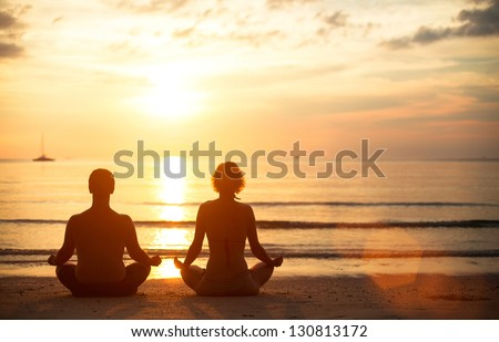 A young couple sitting on the beach of the sea in the lotus position at sunset, yoga practice - stock photo