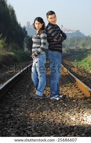 A young couple standing on a railway track - stock photo