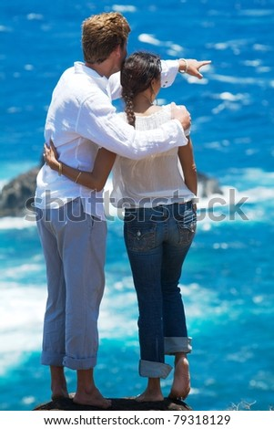 A young couple stands at the top of a cliff overlooking the ocean. The man is pointing to something in the distance. Vertical image orientation. - stock photo