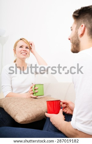 A young couple talking with coffee on the Sofa.   - stock photo