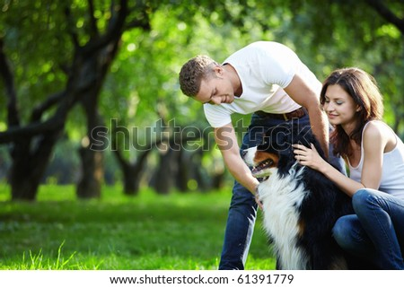 A young couple walking a dog in the park - stock photo