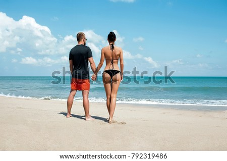 A young couple walking along a beach. A loving couple holding hands looks into the distance of the ocean.