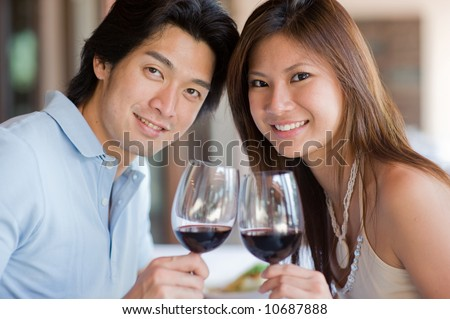 A young couple with red wine at a restaurant - stock photo