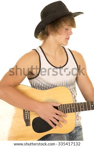 A young cowboy playing his guitar in his western clothes. - stock photo