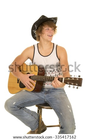 A young cowboy with a big smile playing his guitar. - stock photo