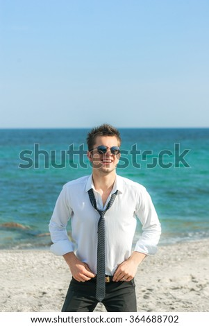 a young cute men at the beach, pretty young bridegroom jokes and fooling around with a tie, dressed in a white shirt and black  stylish black tie and fashionable glasses