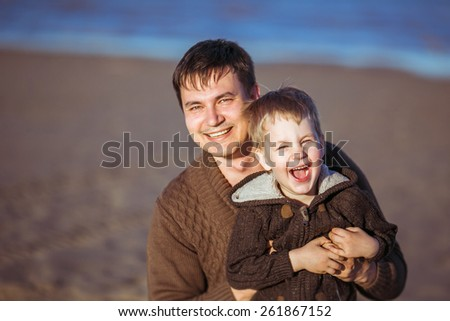 A young dark-haired man is smiling and embracing his five-year-old laughing son. Clothes: casual. - stock photo