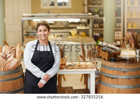A young deli employee standing in front of the pastry display - stock photo