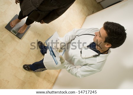 A young doctor, checks his patients weight on a scale. - horizontally framed - stock photo
