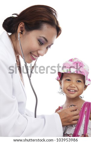 A young doctor examining child with stethoscope at medical office - stock photo