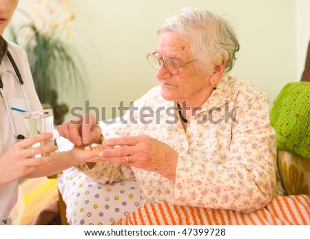 A young doctor giving medications - drugs and vitamins - and a glass of fresh water to an elderly woman.
