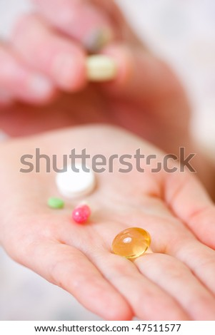 A young doctor giving medications - drugs and vitamins - and a glass of fresh water to an elderly woman - focus on the vitamin pill. - stock photo