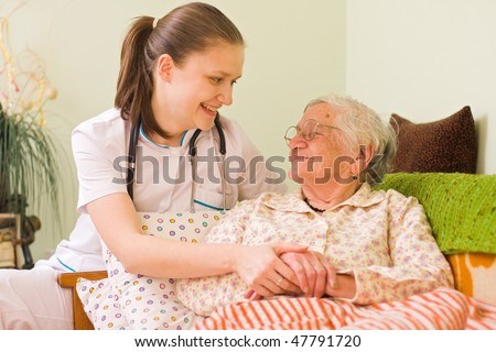 A young doctor / nurse visiting an elderly sick woman holding her hands with caring attitude. - stock photo