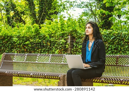 A young East Indian American college student sitting on chairs on green campus, working on laptop computer, looking up, thinking. Concept of environment protection, new technology in our daily life. - stock photo