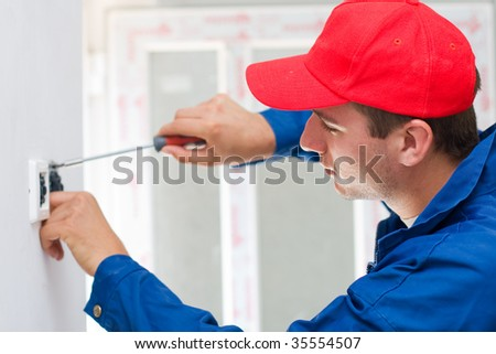 A young electrician installing an electrical switch in a new house. - stock photo