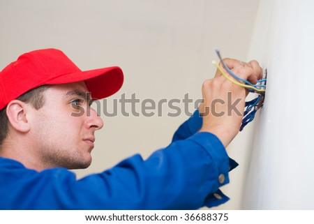A young electrician insulating the electric wires of an electric box. - stock photo