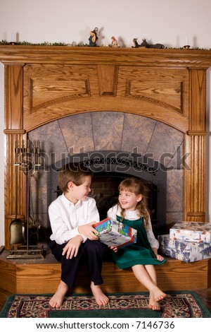 A young elementary boy sitting on a hearth giving his little sister a wrapped Christmas gift.
