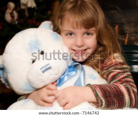 A young elementary girl hugging a giant blue and white teddy bear in front of a Christmas tree and fireplace.