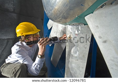 young engineer inspecting the blades of an industrial wind tunnel