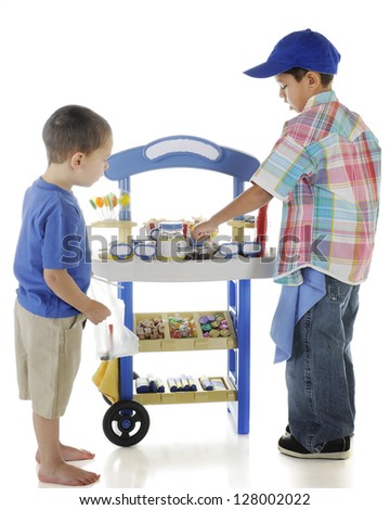 A young entrepreneur tending his candy stand while a preschool customer checks out the goods.  On a white background. - stock photo
