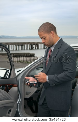 A young ethnic businessman types an appointment into his PDA device.
