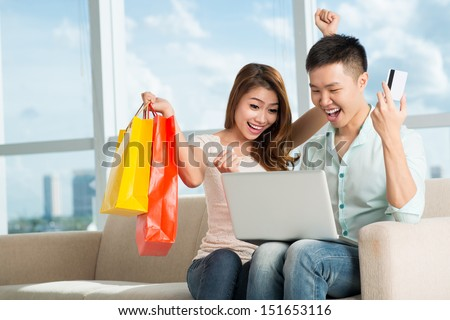 A young excited couple buying something using Internet at home
