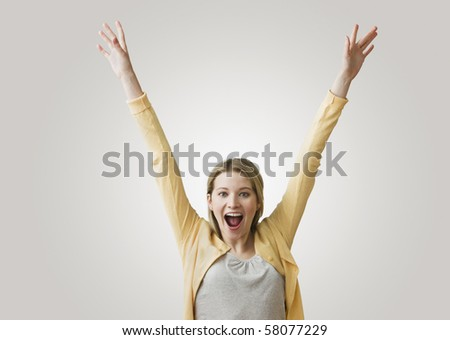 A young, excited woman has her arms outstretched in the air as she smiles at the camera.  Horizontal shot. - stock photo