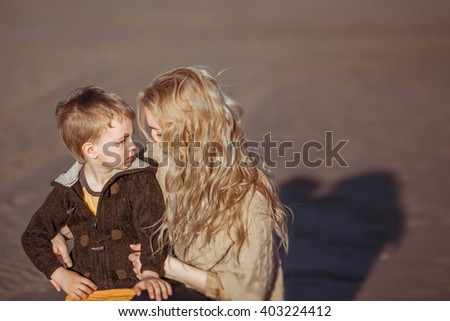 A young fair-haired woman is sitting on her haunches on the sand in a sunny day and embracing her small son, who's looking at her. Clothes: casual. - stock photo
