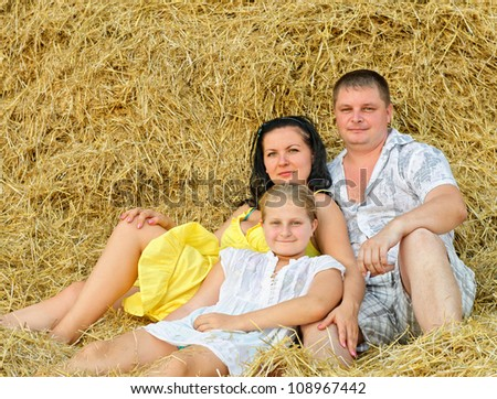 A young family, father, mother and daughter. On the background of the large stack of hay - stock photo