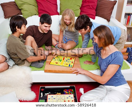 a young family is playing board-games in their bed - stock photo
