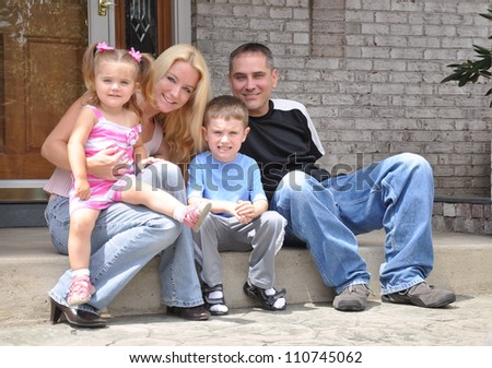 A young family is sitting in front of a home smiling and posing. There is a mother, daughter, father and son. Use it for a love or real estate concept. - stock photo