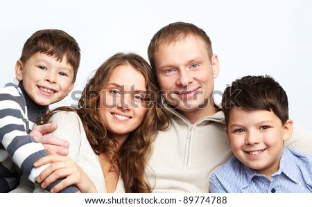 A young family of father, mother and two kids looking at camera and smiling - stock photo
