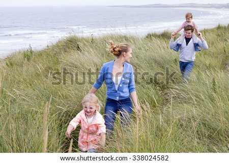 A young family of four running through long grass next to the beach. They are wearing casual clothing and are smiling.  - stock photo