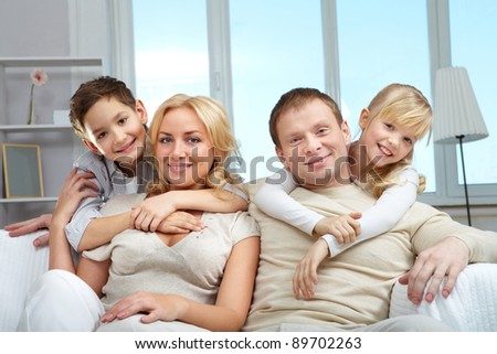 A young family of four sitting on sofa, looking at camera and smiling
