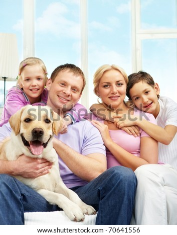 A young family of four with a dog sitting on sofa, looking at camera and smiling - stock photo