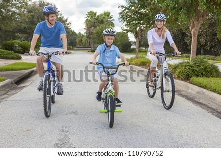 A young family of man and woman parents and one boy child, cycling together. - stock photo