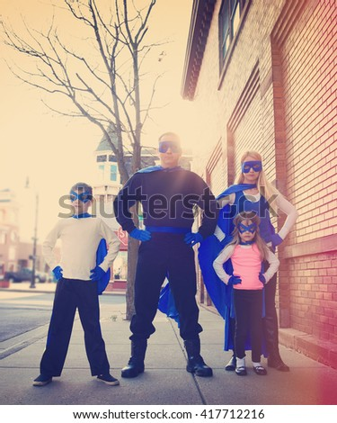 A young family of super heroes are standing outside with blue capes and masks for a protection, strength or happiness concept