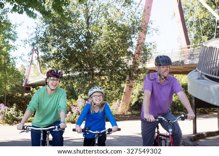 A young family ride along the bike path at Alton Baker Park by the DeFazio bike bridge in Eugene Oregon - stock photo