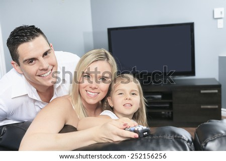 A Young family watching TV together at home - stock photo