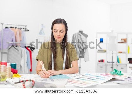a young fashion designer drawing at the desk in her showroom