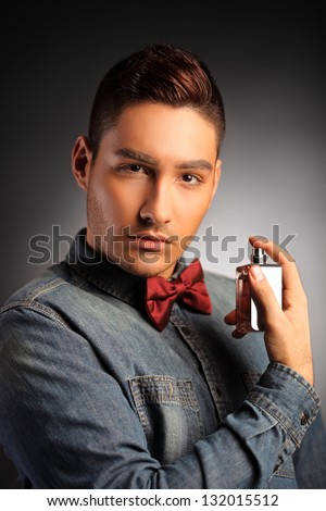 A young fashionable guy applying a parfume and looking at camera - stock photo