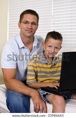 A young father and his son use a laptop to look something up on the internet. - stock photo