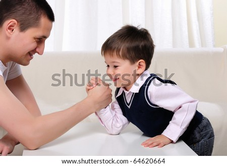 A young father and his young son struggling in the arms