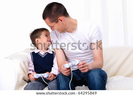 A young father and son together playing video games - stock photo